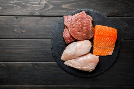 Photo for Top view of fresh raw salmon, meat and chicken breasts on wooden black table, ketogenic diet menu - Royalty Free Image