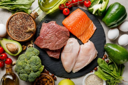Photo for Top view of raw meat and fish among fresh vegetables, ketogenic diet menu - Royalty Free Image