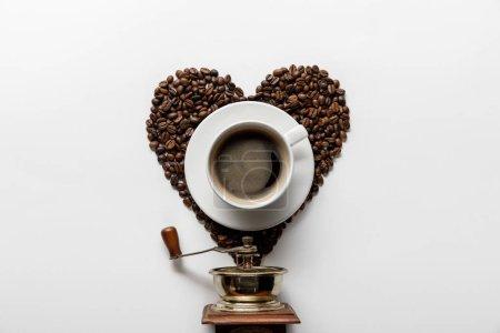 Photo pour Vue supérieure du café dans la tasse sur la soucoupe avec le coeur fait des grains de café près du moulin à café de cru sur le fond blanc - image libre de droit
