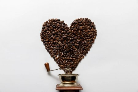 top view of heart made of coffee grains near vintage coffee grinder on white background