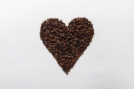 Photo pour Vue supérieure du coeur fait des grains frais de café sur le fond blanc - image libre de droit