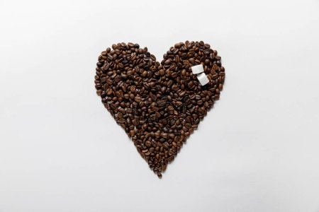 Photo for Top view of heart made of coffee grains with sugar on white background - Royalty Free Image