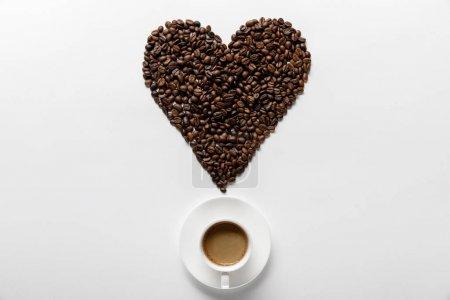 Photo pour Vue supérieure du café délicieux dans la tasse sur la soucoupe avec le coeur fait des grains de café sur le fond blanc - image libre de droit