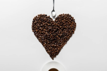top view of coffee in cup on saucer with heart made of coffee grains near spoon on white background