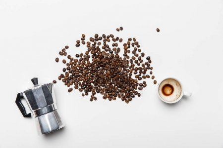 top view of aluminium coffee pot, scattered coffee grains and cup on white background