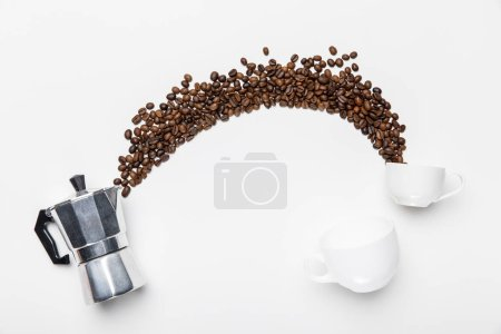top view of aluminium coffee pot, coffee grains and cups on white background