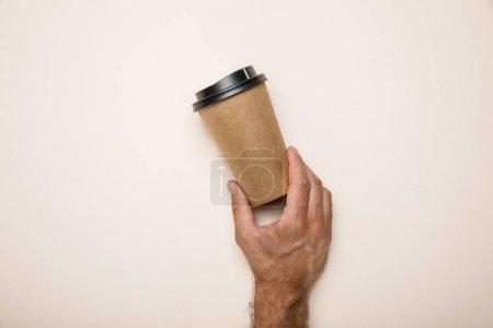 Photo pour Vue recadrée de l'homme retenant la tasse de papier sur le fond beige - image libre de droit