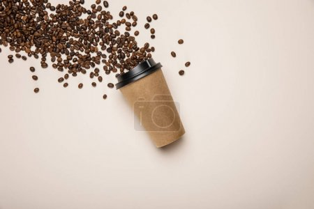 Photo for Top view of coffee to go and scattered fresh coffee beans on beige background - Royalty Free Image
