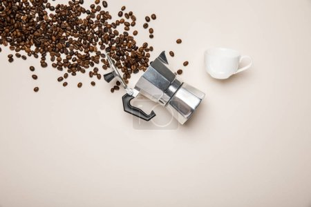 Photo for Top view of aluminium coffee pot, cup and fresh coffee beans on beige background - Royalty Free Image