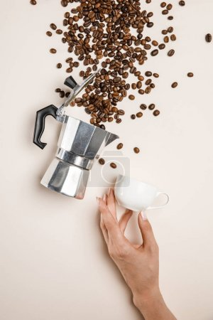Photo for Partial view of woman holding cup near aluminium coffee pot and scattered fresh coffee beans on beige background - Royalty Free Image