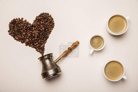 Photo pour Vue supérieure des tasses avec le café près du coeur fait des grains de café et du cezve sur le fond beige - image libre de droit