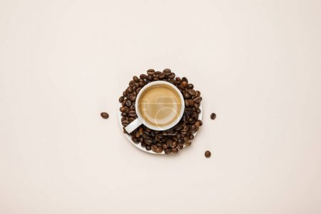 Photo for Top view of cup with delicious coffee on coffee grains on beige background - Royalty Free Image