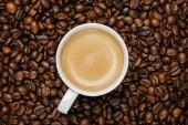 """Постер, картина, фотообои """"верхний вид вкусного кофе в белой чашке на свежих кофейных зернах"""""""