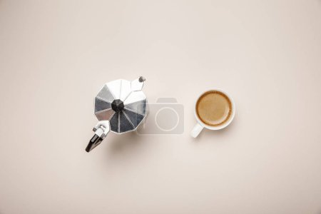Photo for Top view of metal coffee pot and delicious coffee in cup on beige background - Royalty Free Image