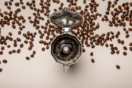 Photo for Top view of opened metal coffee pot with fresh coffee near coffee beans on beige background - Royalty Free Image