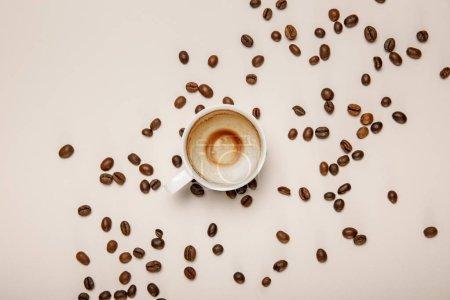 Foto de Vista superior de la taza de café con espuma sobre fondo beige con granos de café - Imagen libre de derechos