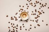 """Постер, картина, фотообои """"верхний вид кофейной чашки с пеной на бежевом фоне с кофейными зернами"""""""