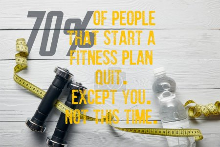 Foto de Top view of bottle with water, measuring tape and dumbbells on wooden white background with 70% of people that start a fitness plan quit, except you, not this time illustration - Imagen libre de derechos