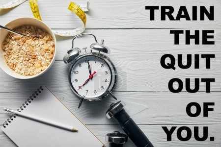 Photo for Top view of silver alarm clock, notebook with pencil, breakfast cereal, measuring tape, dumbbells on wooden white background with train the quit out of you lettering - Royalty Free Image