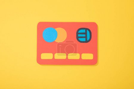 top view of red paper icon of credit card isolated on yellow