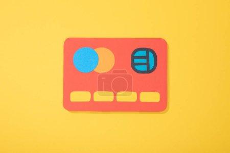 Photo pour Vue du haut de l'icône en papier rouge de la carte de crédit isolée sur jaune - image libre de droit