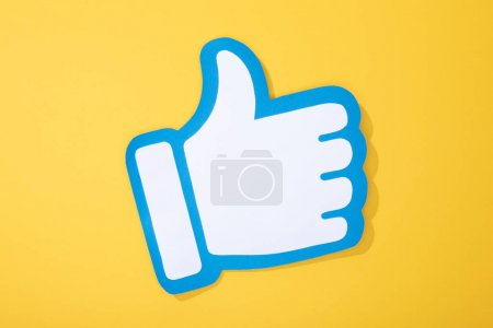 top view of white paper hand with thumb up on yellow background
