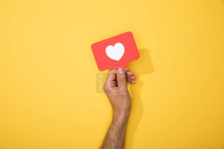 Photo for Cropped view of man holding paper icon with white heart - Royalty Free Image