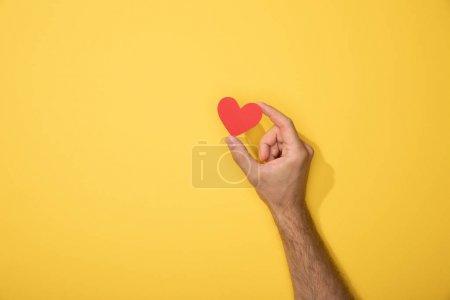 Photo pour Vue recadrée de l'homme retenant le coeur rouge de papier sur le jaune - image libre de droit