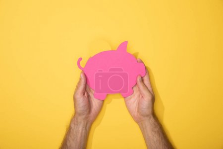 Photo for Cropped view of man holding pink paper piggy bank on yellow - Royalty Free Image