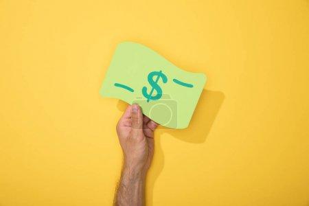 Photo pour Vue recadrée de l'homme retenant l'icône de papier de billet de banque de dollar sur le jaune - image libre de droit