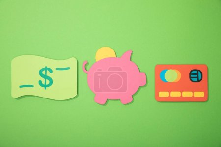 flat lay with piggy bank, credit card and dollar banknote isolated on green