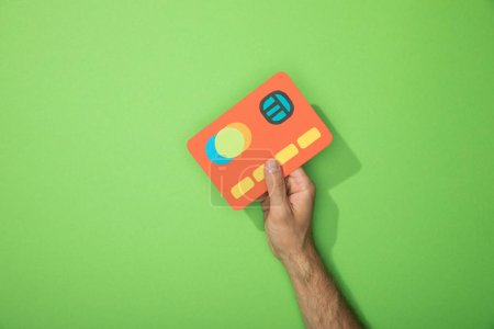 Photo for Cropped view of man holding red paper icon of credit card on green - Royalty Free Image