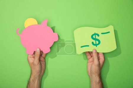 Photo pour Vue recadrée de l'homme tenant des icônes en papier de tirelire et billet en dollar sur vert - image libre de droit