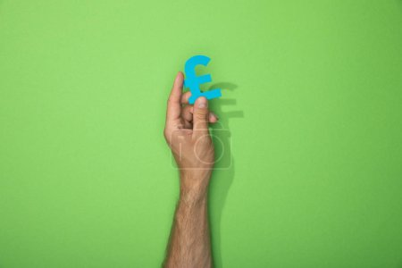 Photo pour Vue recadrée de l'homme retenant l'icône de papier du signe de devise de livre sur le vert - image libre de droit