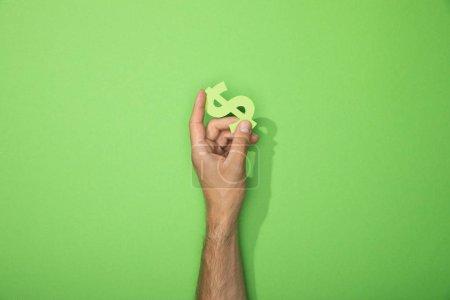 Photo pour Vue recadrée de l'homme tenant signe de devise dollar sur vert - image libre de droit