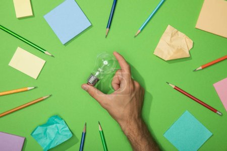 Photo for Cropped view of man holding light bulb near scattered pencils and crumpled paper on green - Royalty Free Image