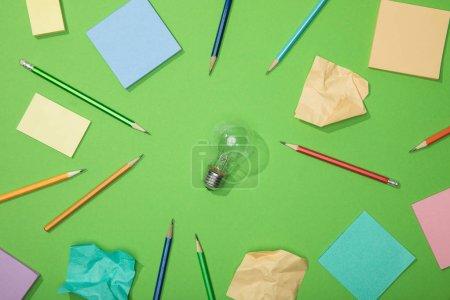 Foto de Vista superior de la bombilla cerca de lápices dispersos y papel arrugado en verde - Imagen libre de derechos