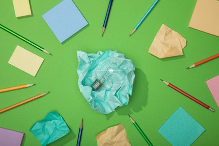 Photo for Top view of light bulb on piece of crumpled paper near scattered paper and pencils on green - Royalty Free Image