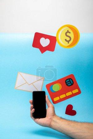 Photo pour Vue recadrée de l'homme tenant smartphone près d'icônes en papier coloré sur fond bleu et gris - image libre de droit