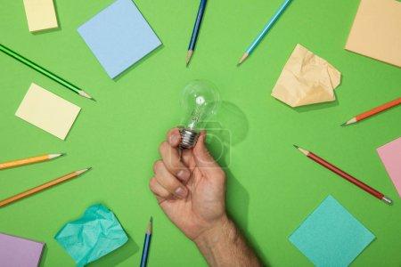Photo pour Vue recadrée de l'homme retenant l'ampoule près des crayons et du papier sur le vert - image libre de droit