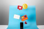 """Постер, картина, фотообои """"смартфон возле красочных бумажных иконок на синем и сером фоне"""""""
