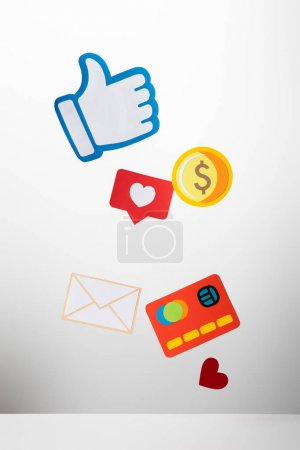 colorful paper cut with envelope, coin, credit card, hearts and thumb up on white background