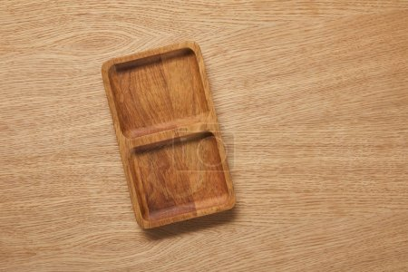 Photo for Top view of wooden empty plate on wooden table - Royalty Free Image