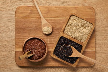 Photo for Top view of white, black and red quinoa on wooden chopping board - Royalty Free Image