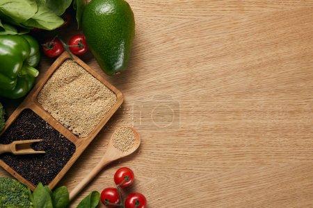 Foto de Vista superior de la quinua blanca y negra en cuencos cerca de verduras maduras y cuchara en la mesa de madera - Imagen libre de derechos