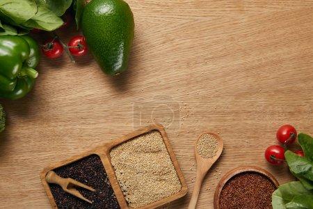 Photo pour Vue supérieure du quinoa blanc, rouge et noir dans des cuvettes près des légumes mûrs et de la cuillère sur la table en bois - image libre de droit