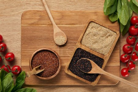Photo for Top view of white, black and red quinoa in wooden bowl on chopping board near spinach leaves and tomatoes - Royalty Free Image