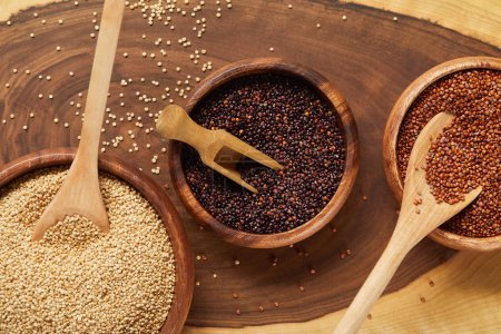 Photo for Close up view of white, black and red quinoa seeds in wooden bowls with spatula and spoons - Royalty Free Image