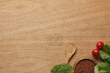Photo for Top view of white and red quinoa in wooden bowl and spoon near vegetables - Royalty Free Image