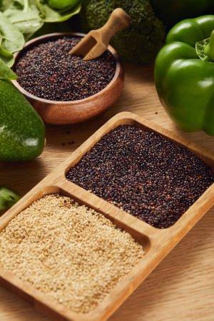 Photo pour Graines de quinoa noir et blanc dans des bols en bois avec spatule près des légumes verts - image libre de droit